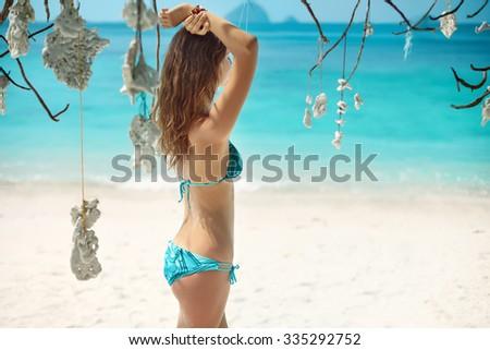 Beautiful girl in bikini relaxing on the tropical paradise beach. summer vacation - stock photo