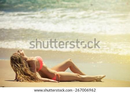 Beautiful girl in bikini sunbathing on the beach - stock photo