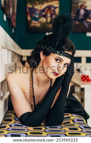 Beautiful girl in black dress and gloves lies on the bench. Party in style gangsters forties. - stock photo