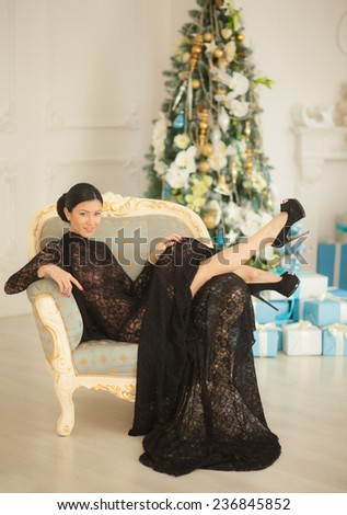 Beautiful girl in black dress sitting in a chair on the background of the Christmas tree. - stock photo