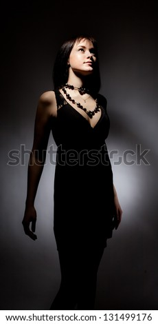 Beautiful girl in black dress standing on black background.