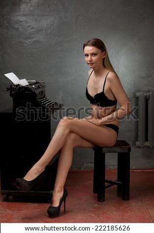 Beautiful girl in black lingerie working on a typewriter on a gray background.
