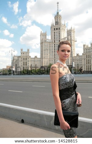 beautiful girl in black-silvery dress on background of the old moscow skyscraper