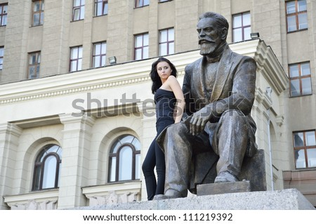 Beautiful girl in black tight clothing  posing near monument