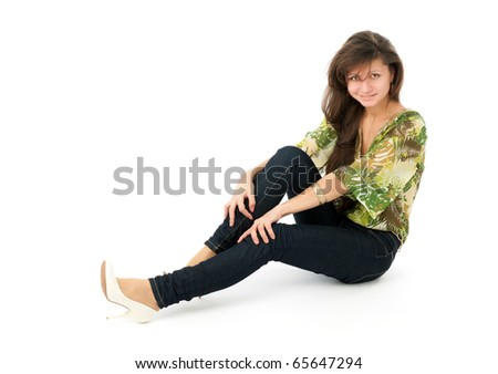 Beautiful girl in blue jeans sitting on a floor
