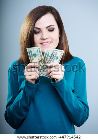 beautiful girl in blue shirt counts money, on a gray background - stock photo