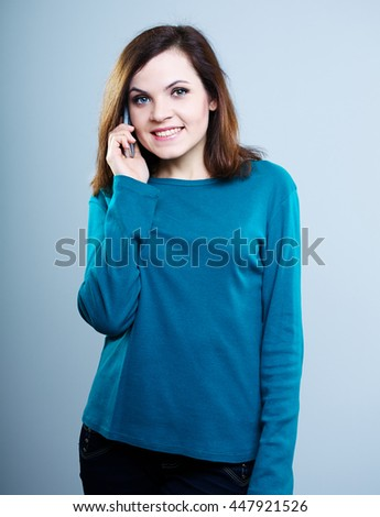 beautiful girl in blue shirt talking on the phone and smiling