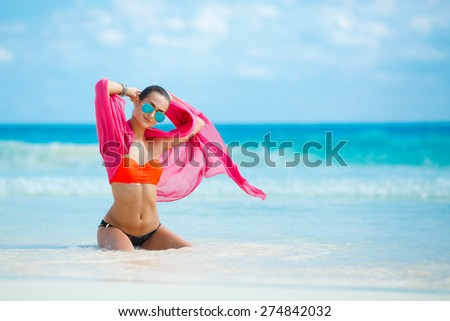 Beautiful girl in blue sunglasses sits on white sand beach on background of blue sea and sky. summer holidays and vacation - girl sitting on the beach near ocean. Sexy young woman - stock photo