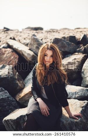 Beautiful girl in bright dress on stones - stock photo