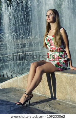 Beautiful girl in bright dress sitting on stone parapet near the fountain - stock photo
