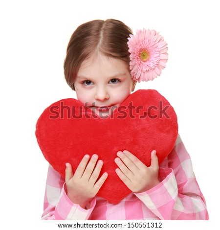 Beautiful girl in casual wear with gerberas in her hair holding a big red heart on a white background