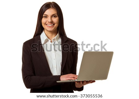 Beautiful girl in classical suit using a laptop, looking in camera and smiling while standing isolated on a white background