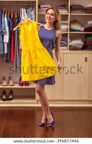 Beautiful girl in cocktail dress is smiling and looking at camera while choosing another dress in her dressing room - stock photo