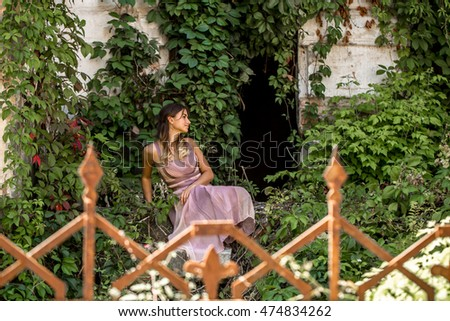 beautiful girl in dress on the background of wild grapes and an old house with wooden doors