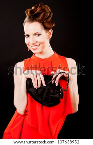 Beautiful girl in evening dress holding a purse - stock photo