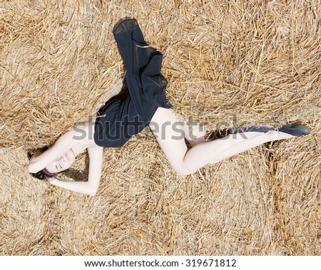 beautiful girl in evening dress summer day asleep on a huge haystack.top view.toned - stock photo