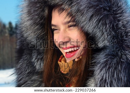 Beautiful girl in fur coat with hood laughs outdoor in sunny winter day - stock photo