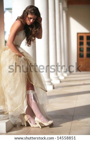 beautiful girl in gown of the bride corrects white golfs with bow - stock photo