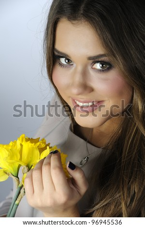 Beautiful girl in gray dress with bouquet of yellow daffodils