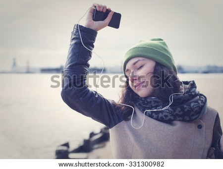 Beautiful girl in green cap and leather jacket fun and dancing to the music. - stock photo