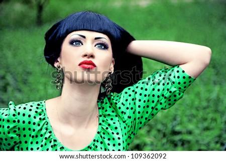 Beautiful girl in green dress in summer garden - stock photo