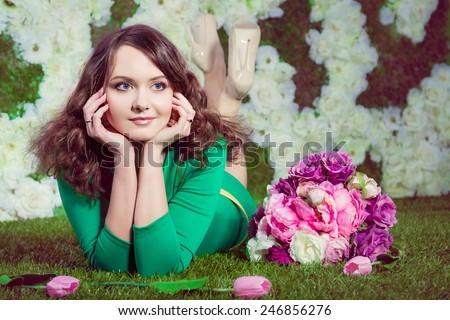Beautiful girl in green dress with flowers in studio - stock photo