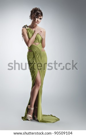 beautiful girl in green evening gown posing against gray background - stock photo