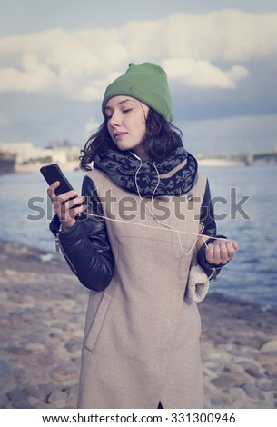 Beautiful girl in green hat and coat reads the message and listening to music with headphones in the city of St. Petersburg. - stock photo