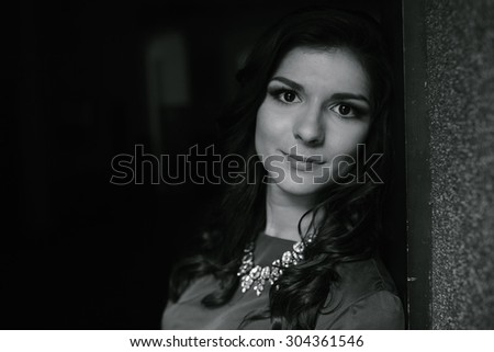 beautiful girl in green standing in the doorway and smiles - stock photo