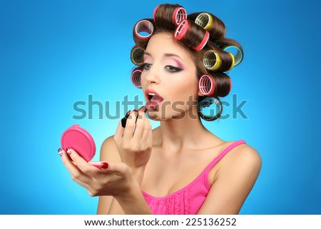 Beautiful girl in hair curlers on blue background - stock photo