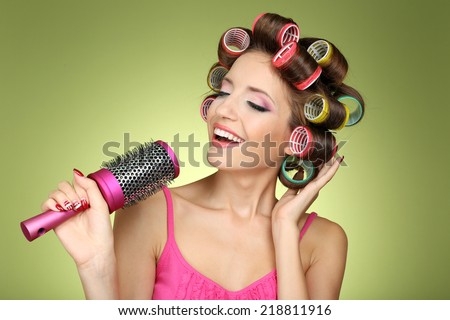 Beautiful girl in hair curlers on green background - stock photo