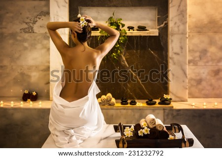 Beautiful girl in hammam. Tray with towels and flowers. - stock photo