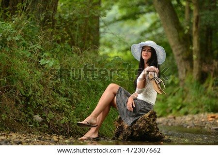 Beautiful girl in hat smiling at the summer
