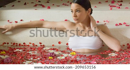 Beautiful girl in jacuzzi with rose petal - stock photo