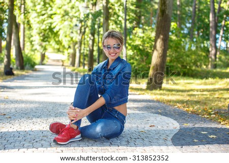 Beautiful girl in jeans pants and jeans jacket sitting on the road in a park.