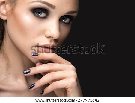 "Beautiful girl in leather jacket with bright makeup and manicure ""Cat's Eye"". Beauty face. Nail Design. Picture taken in the studio on a black background. - stock photo"