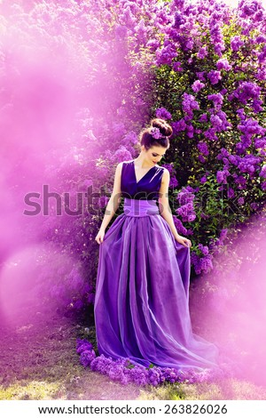 Beautiful girl in lilac ball dress among the flowers in the garden