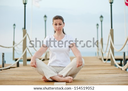 beautiful girl in lotus position resting on the pier at the sea - stock photo