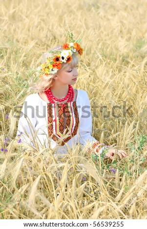 beautiful girl in national costume in a field of wheat - stock photo