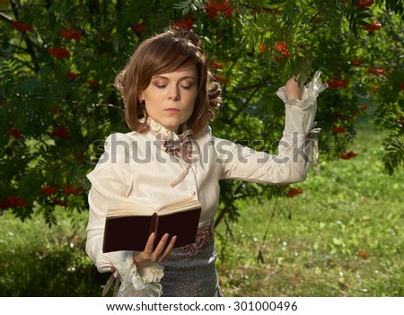 Beautiful girl in old style clothing touches rowan berries and reads book                               - stock photo