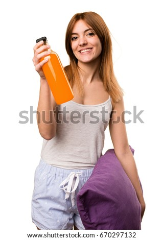 Beautiful girl in pajamas holding an orange juice