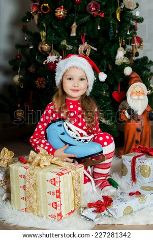 Beautiful girl in pajamas  with skate in the hands is waiting Christmas and New year celebration under X-mas tree, portrait
