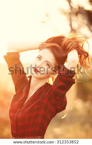 Beautiful girl in plaid dress on sunset at countryside