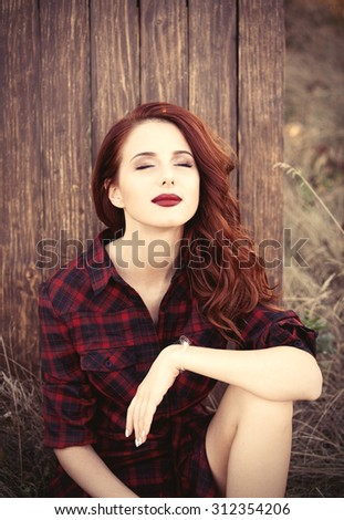 Beautiful girl in plaid dress sitting near a wooden background at countryside  - stock photo