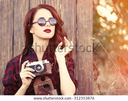 Beautiful girl in plaid dress with camera and sunglasses on wooden background. - stock photo