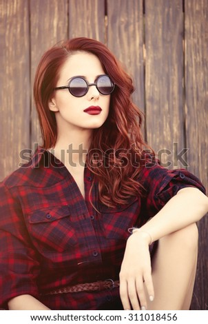 Beautiful girl in plaid dress with sunglasses on wooden background at countryside  - stock photo
