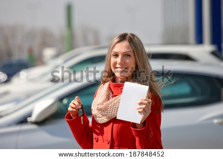 Beautiful girl in red coat holds  keys to a new car. Buying a car - stock photo