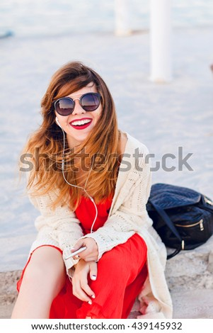 Beautiful girl in red dress and white jacket sits on a pier, smiles widely, and listens to music on earphones on a smartphone. Girl has ombre hair. She wears dark sunglasses.