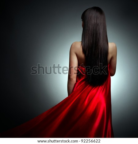 Beautiful girl in red dress back on black background - stock photo