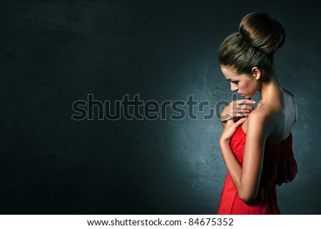 Beautiful girl in red dress over on black background - stock photo